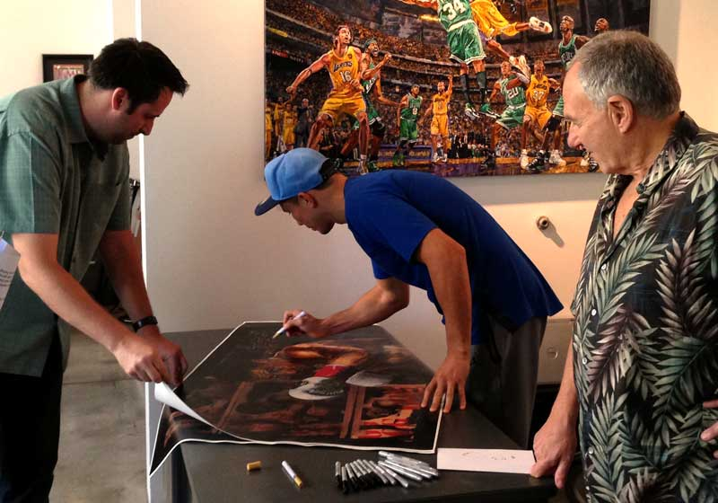 Gennady Golovkin signs limited edition prints of portriat, as artist Stephen Holland looks on.